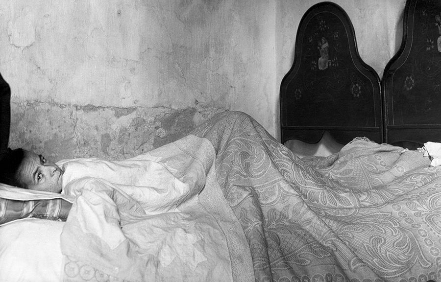 Partinico. Ill woman in bed, 1954